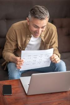 Radosny mężczyzna trzyma arkusz z tekstem w pobliżu notatnika