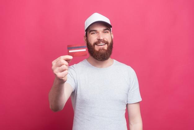 Radosny mężczyzna uśmiecha się i pokazuje kartę kredytową z brodą