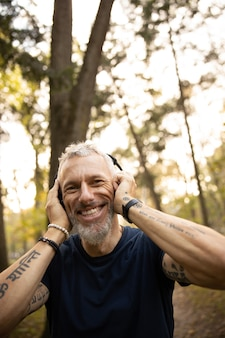 Radosny mężczyzna w słuchawkach biegający w lesie