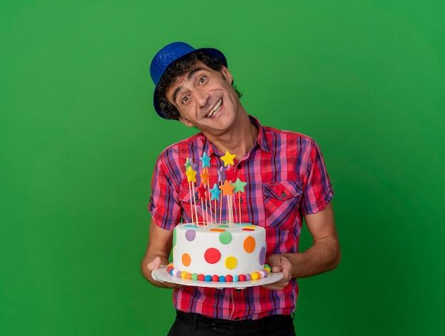Radosny mężczyzna w średnim wieku kaukaski strona ubrana w kapelusz strony gospodarstwa tort urodzinowy, patrząc na kamery na białym tle na zielonym tle z miejsca na kopię