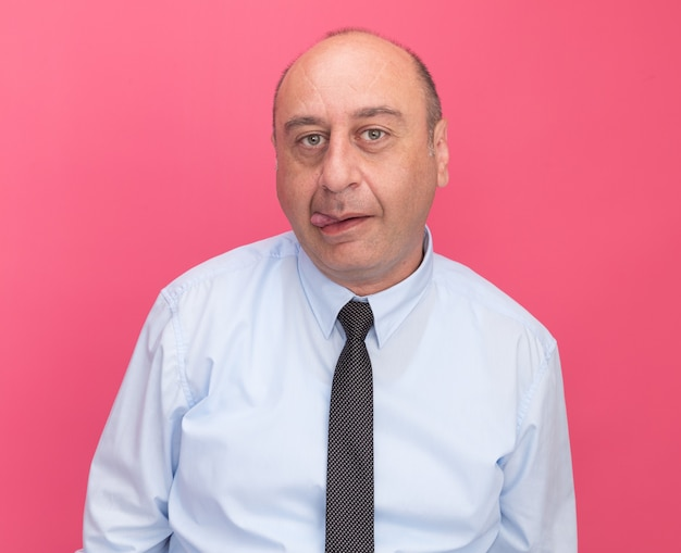 Radosny mężczyzna w średnim wieku ubrany w białą koszulkę z krawatem przedstawiający język na różowej ścianie