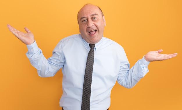 Radosny mężczyzna w średnim wieku ubrany w białą koszulkę z krawatem, rozkładając ręce na białym tle na pomarańczowej ścianie