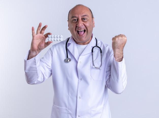 """Radosny mężczyzna w średnim wieku, ubrany w szatę medyczną i stetoskop pokazujący paczkę tabletek, patrzący z przodu, robiący gest """"tak"""" na białym tle na białej ścianie"""