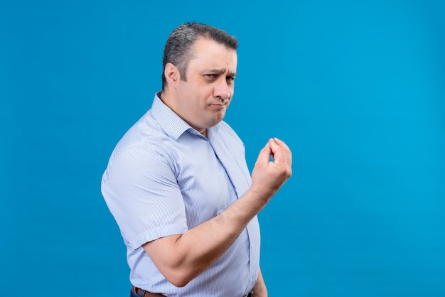 Radosny mężczyzna w średnim wieku w niebieskiej koszuli w pionowe paski pokazujący pyszny gest ręką na niebieskim tle