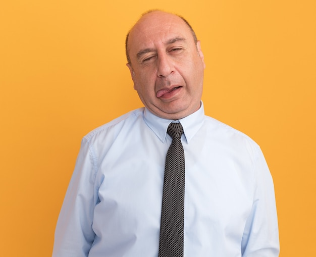 Radosny mężczyzna w średnim wieku z przechylaną głową w białej koszulce z krawatem pokazującym język na pomarańczowej ścianie