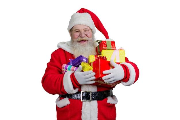 Radosny mikołaj trzyma prezenty świąteczne.