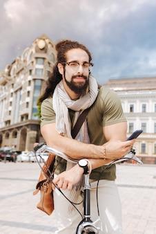 Radosny miły mężczyzna patrzy na ciebie stojąc ze swoim rowerem