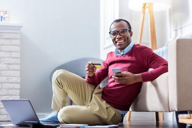 Radosny miły pozytywny mężczyzna trzyma kartę kredytową i uśmiecha się, siedząc na podłodze przed swoim laptopem