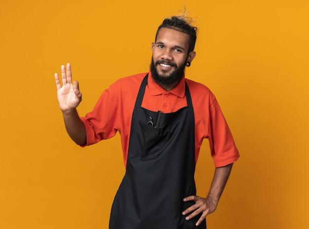 Radosny młody afro-amerykański fryzjer męski noszący mundur trzymający rękę w talii, robiący ok znak na pomarańczowej ścianie z kopią miejsca