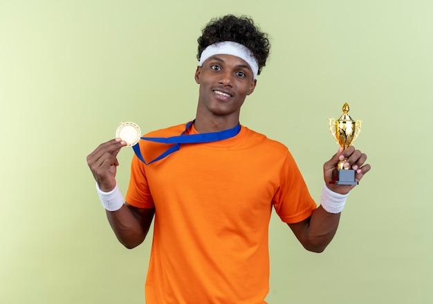 Radosny młody afro-amerykański sportowy mężczyzna ubrany w opaskę i opaskę oraz medal trzymając kubek na białym tle na zielonej ścianie