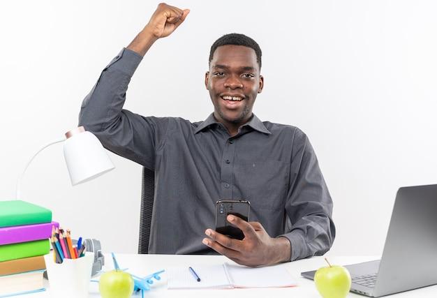 Radosny młody afroamerykański uczeń siedzący przy biurku z szkolnymi narzędziami trzymający telefon i podnoszący pięść w górę