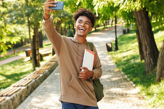 Radosny młody afrykanin z plecakiem spacerujący po parku