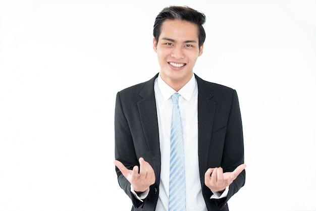 Radosny młody biznesmen azji gestykuluje