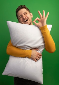 Radosny młody blond przystojny mężczyzna przytulający poduszkę robi ok znak