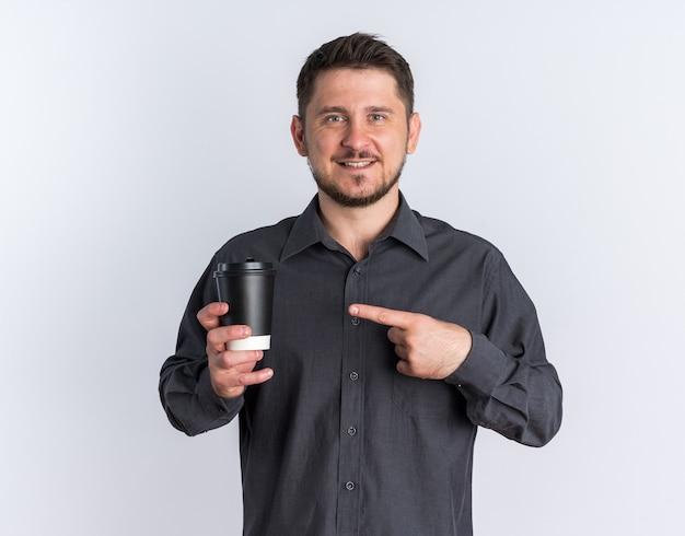 Radosny młody blond przystojny mężczyzna trzymający i wskazujący na filiżankę kawy, patrząc na kamerę