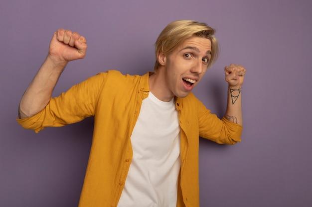 Radosny młody blondyn na sobie żółtą koszulkę, podnosząc ręce na białym tle na fioletowo z miejsca na kopię