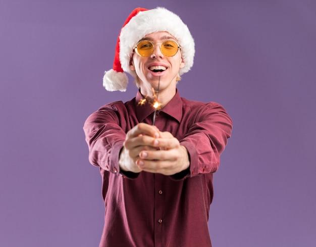 Radosny młody blondyn w kapeluszu santa i okularach wyciągając brylant wakacje na białym tle na fioletowej ścianie z miejsca na kopię