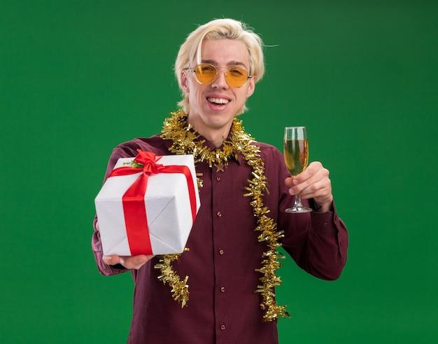 Radosny młody blondyn w okularach z świecącą girlandą na szyi trzyma kieliszek szampana i wyciąga pakiet prezentów na zielonej ścianie