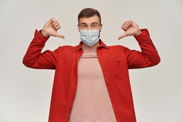 Radosny młody brodaty mężczyzna w czerwonej koszuli i masce chroniącej przed wirusem na twarzy przed koronawirusem wskazującym na siebie dwoma kciukami na białej ścianie