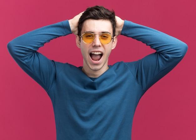 Radosny młody brunetka kaukaski chłopiec w okularach przeciwsłonecznych kładzie ręce na głowie patrząc na kamery na różowo