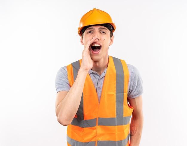 Radosny młody budowniczy mężczyzna w mundurze wzywający kogoś