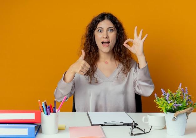 Radosny młody całkiem żeński pracownik biurowy siedzi przy biurku z narzędzi biurowych pokazując okey gest jej kciuk w górę na białym tle na pomarańczowej ścianie