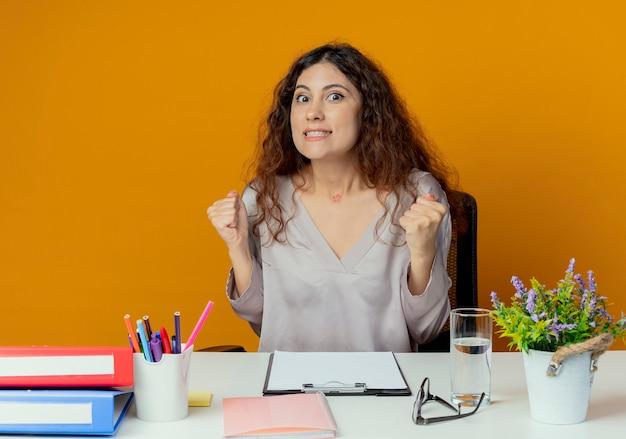 Radosny młody całkiem żeński pracownik biurowy siedzi przy biurku z narzędzi biurowych pokazując tak gest na białym tle na pomarańczowym tle