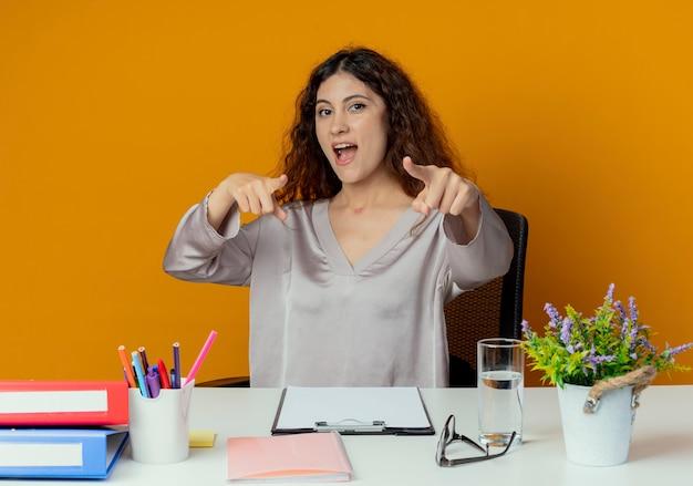 Radosny młody całkiem żeński pracownik biurowy siedzi przy biurku z narzędzi biurowych punktów na aparat na białym tle na pomarańczowym tle