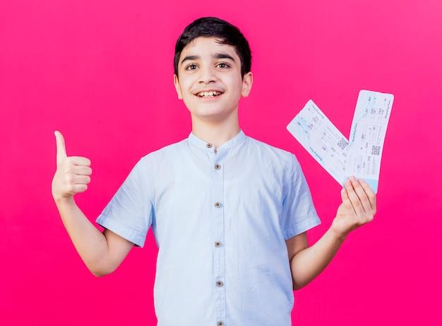 Radosny młody chłopiec kaukaski patrząc prosto trzymając bilety lotnicze pokazując kciuk w górę na białym tle na szkarłatnym tle