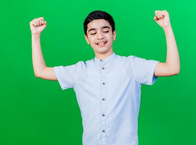 Radosny młody chłopiec kaukaski patrząc w dół robi tak gest na białym tle na zielonej ścianie