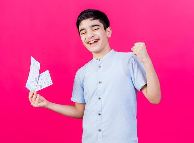 Radosny młody chłopiec kaukaski trzymając bilety lotnicze robi gest tak z zamkniętymi oczami na białym tle na szkarłatnym tle