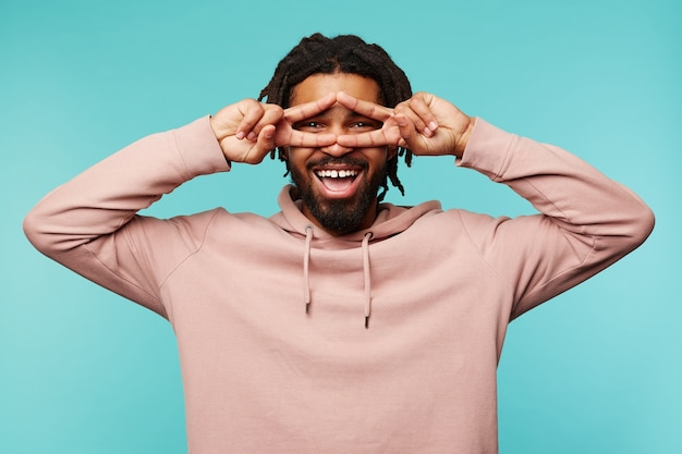 Radosny młody ciemnoskóry brunet mężczyzna z dredami podnoszący ręce z gestem zwycięstwa do twarzy i patrząc wesoło w kamerę z szerokim uśmiechem, odizolowany na niebieskim tle