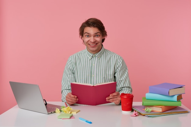 Radosny młody ciemnowłosy uśmiechnięty szeroko czytając notatki, pozujący w pasiastej koszuli, przygotowujący materiały do zajęć dydaktycznych