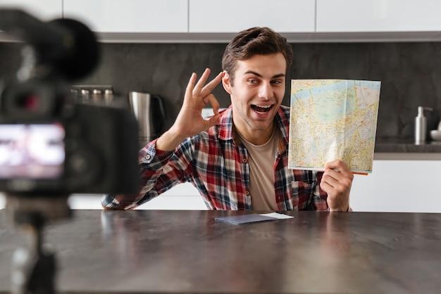 Radosny młody człowiek filmujący swój odcinek blogu wideo