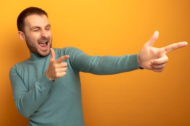 Radosny młody człowiek kaukaski mrugając, patrząc na bok, robi ci gest na białym tle na pomarańczowej ścianie