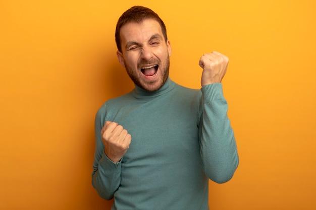 Radosny młody człowiek mrugający z przodu robi gest tak na białym tle na pomarańczowej ścianie