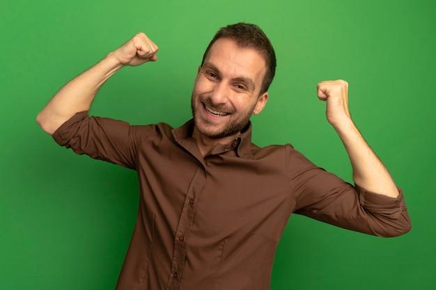 Radosny młody człowiek patrząc z przodu robi tak gest na białym tle na zielonej ścianie