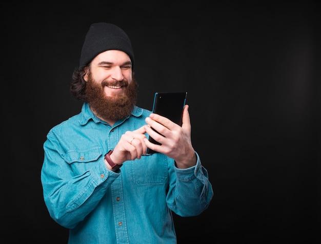 Radosny młody człowiek pisze wiadomość na swoim nowym tablecie w pobliżu ciemnej ściany