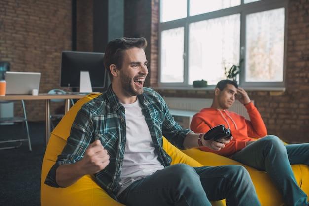 Radosny młody człowiek pokazujący swoje emocje podczas wygrywania gry wideo