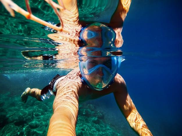 Radosny młody człowiek robi selfie w egzotycznym morzu.