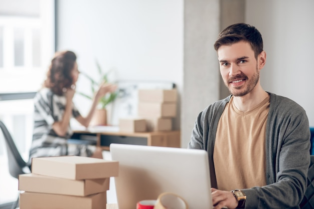 Radosny młody człowiek siedzący przy laptopie w biurze
