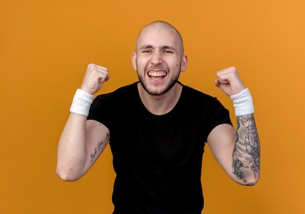 Radosny młody człowiek sportowy na sobie opaskę pokazując silny gest na białym tle na pomarańczowym tle