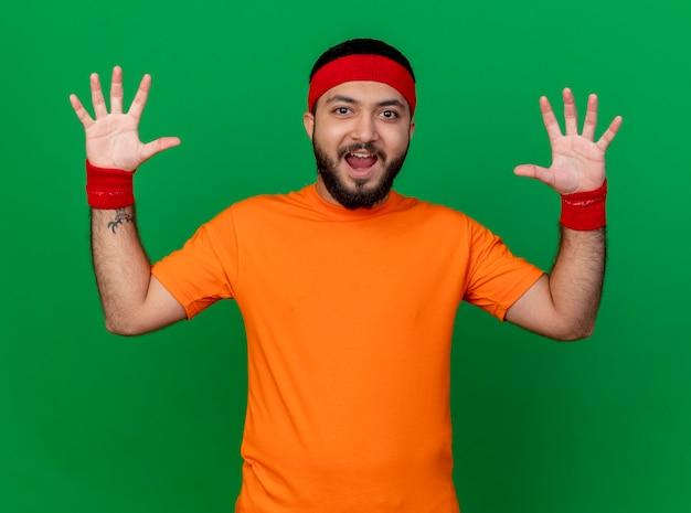 Radosny młody człowiek sportowy noszenia opaski i nadgarstka, podnosząc ręce na białym tle na zielonym tle