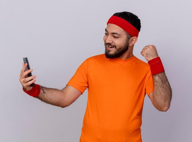 Radosny młody człowiek sportowy noszenia opaski i nadgarstka trzymając