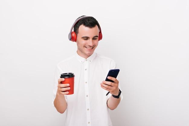 Radosny młody człowiek ubrany w białą koszulę, słucha musiki, trzyma filiżankę kawy i patrzy w telefon.