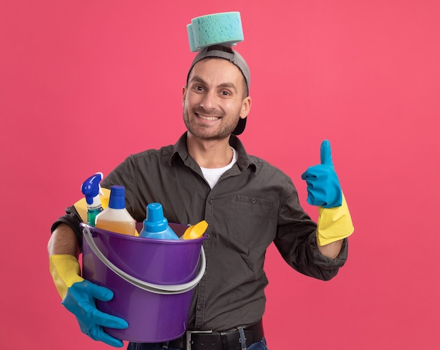 Radosny młody człowiek ubrany w codzienne ubrania i czapkę w gumowych rękawiczkach trzymający wiadro z narzędziami do czyszczenia z gąbką na głowie, uśmiechnięty, pokazujący kciuki do góry, stojący nad różową ścianą