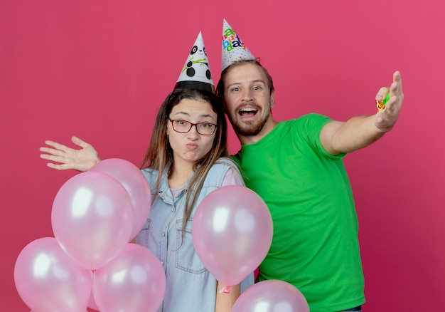 Radosny młody człowiek ubrany w kapelusz partii i zaskoczona młoda dziewczyna stojąca z balonami helowymi na białym tle na różowej ścianie
