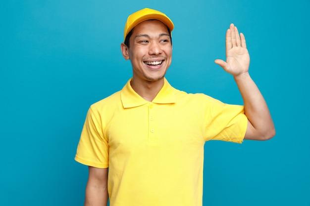 Radosny Młody Człowiek Ubrany W Mundur I Czapkę Dostawy, Patrząc Na Bok, Robi Gest Hi Premium Zdjęcia