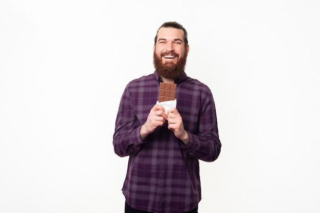 Radosny młody człowiek w kraciastej koszuli, trzymając pasek czekolady i uśmiechnięty