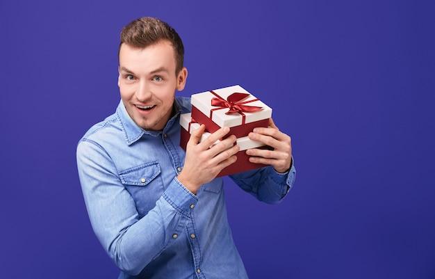 Radosny młody człowiek w niebieskiej dżinsowej koszuli stojący z dwoma prezentami
